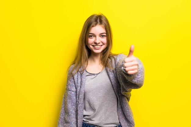 Mensen, gebaar, stijl en manierconcept - gelukkige jonge vrouw of tienermeisje in vrijetijdskleding die duimen opdagen