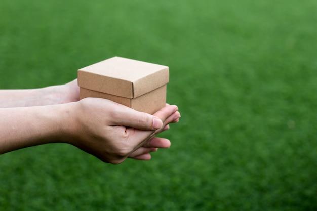 Mensen gebruiken beide handen om kleine bruine geschenkdozen vast te houden, geschenkdozen voor verjaardagen, jubilea en kerstmis. het geven van geschenken op belangrijke dagen en festivals is populair. een belangrijk cadeau-idee voor een dag.
