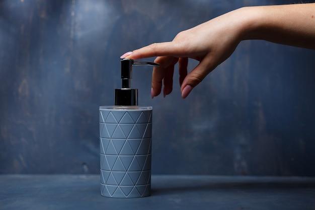 Mensen gebruiken de zeepdispenser met een metalen dop van grijs op een grijze tafel