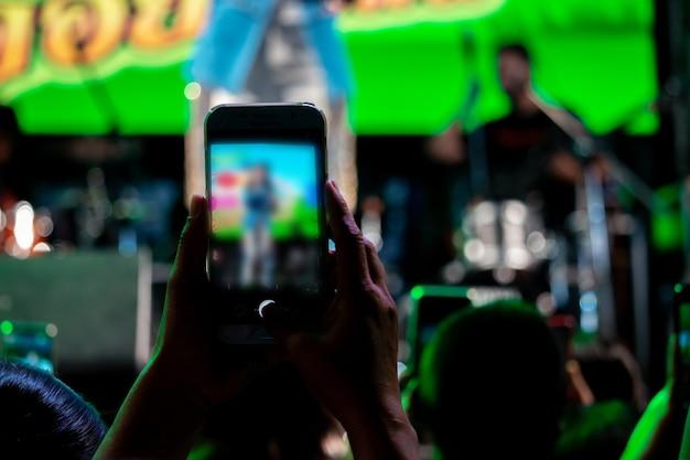 Mensen gebruiken mobiele telefoons om te leven of om foto's te maken bij concerten, 's nachts met felle lichten.