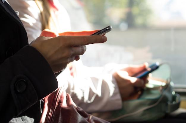 Mensen gebruiken smartphones in het openbaar vervoer. close-up mobiele telefoon in de hand.