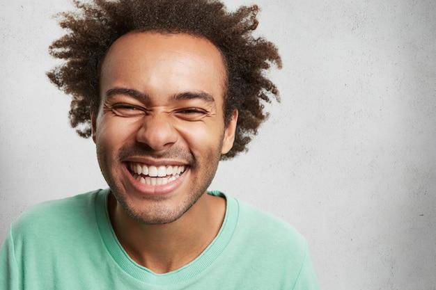 Mensen, geluk en plezierige emoties concept. vrolijke dolblij jonge man met