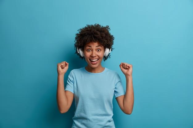 Mensen, geluk, hobby-concept. vrolijke afro-amerikaanse vrouw luistert favoriete audiotrack, geniet van muziek in draadloze koptelefoons, balde vuisten van triomf, glimlacht breed, draagt casual t-shirt