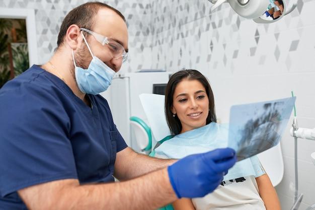 Mensen, geneeskunde, stomatologie en gezondheidszorgconcept - gelukkige mannelijke tandarts die werkplan toont aan vrouwelijke patiënt bij tandkliniekkantoor.