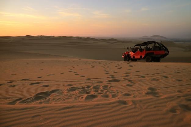 Mensen genieten van duin buggy rijden op huacachina woestijn in ica regio van peru, zuid-amerika