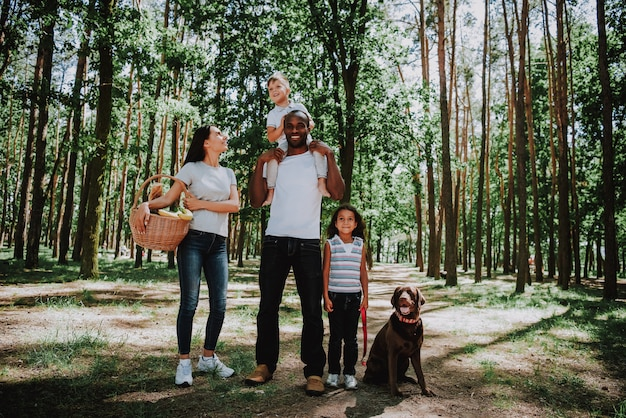 Mensen genieten van wandelen door bos met picknickmand
