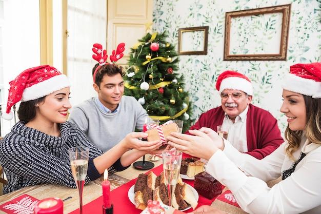 Mensen geven cadeautjes aan elkaar op kerst tafel