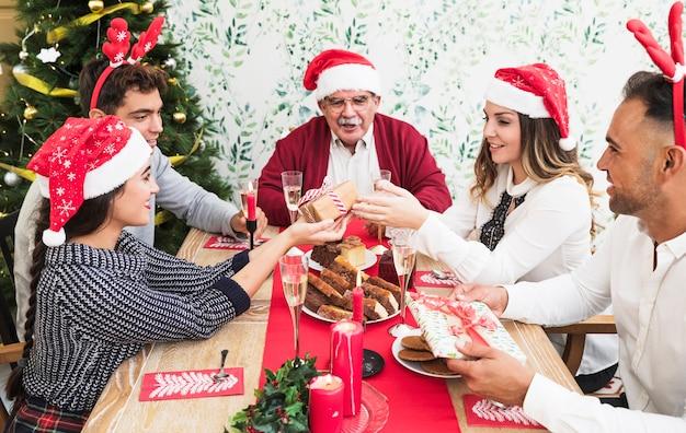 Mensen geven elkaar cadeautjes aan een feestelijke tafel