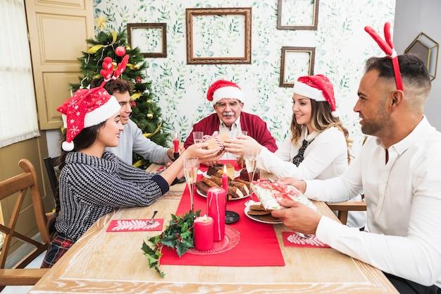 Mensen geven geschenkdozen aan elkaar op feestelijke tafel