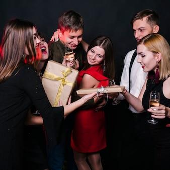 Mensen geven geschenkdozen aan elkaar op feestje