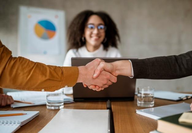 Mensen geven handdruk na een vergadering
