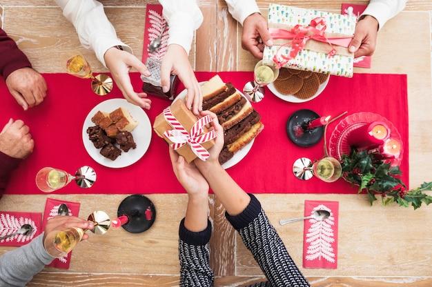 Mensen geven kerst geschenkdozen aan elkaar op feestelijke tafel