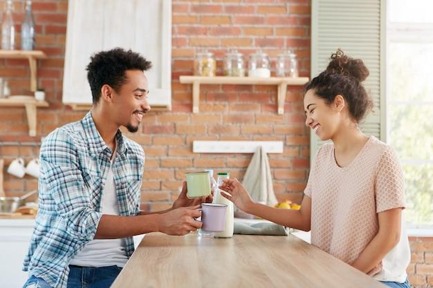 Mensen, gevoelens, relatie. gemengd raspaar brengt vrije tijd samen thuis door, drinkt melk, zit dichtbij lijst