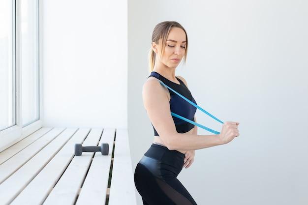 Mensen, gezond en sport concept - fit vrouw in sportkleding gehurkt met band