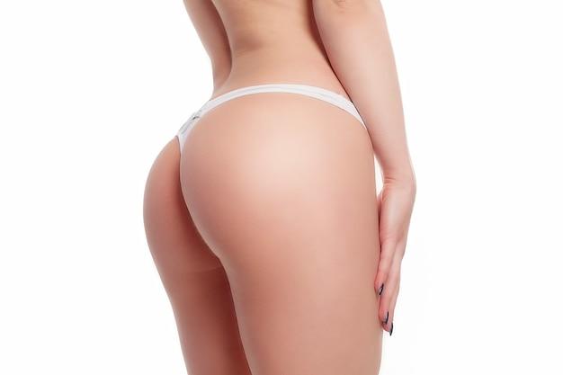 Mensen, gezondheid en lifestyle concept - mooi vrouwenlichaam in vorm. closeup gezond meisje met fit slank lichaam, zachte huid en stevige billen, heupen in witte bikini slipje. strakke grote kont in ondergoed.