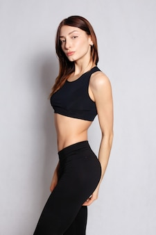 Mensen, gezondheid en lifestyle concept - pretty fit meisje of fitness instructeur poseren en glimlachen geïsoleerd op een witte achtergrond