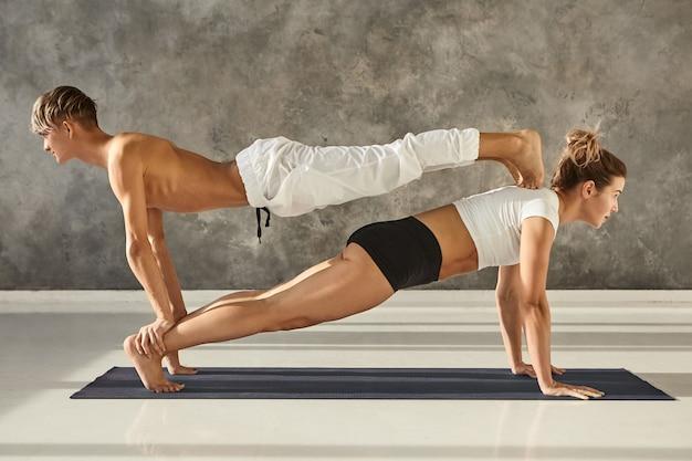 Mensen, gezondheid, sport, activiteit, fitness, pilates en acrobatiekconcept. jonge atletische paar mannelijke en vrouwelijke partner yoga samen beoefenen op sportschool, dubbele plank op een mat doen, man bovenop