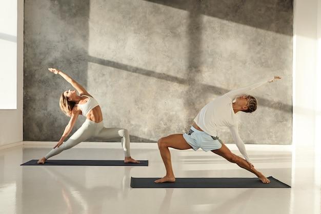 Mensen, gezondheid, sport, welzijn en activiteitenconcept. openhartig schot van jonge man gekleed in korte broek staande op de mat blootsvoets doet yoga asana's met blonde vrouw die beenkappen draagt