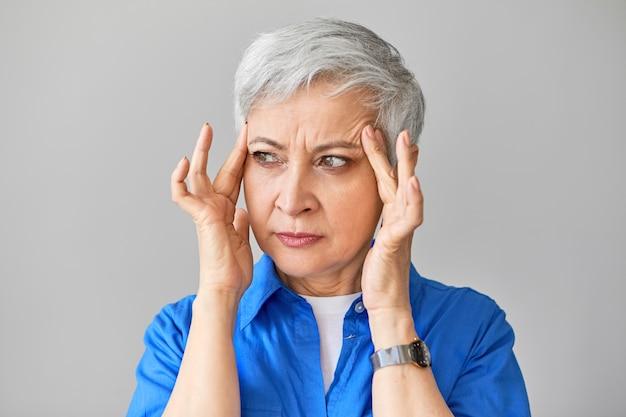 Mensen, gezondheid, stress, leeftijd en volwassenheidsconcept. geïsoleerde shot van gefrustreerde fronsende europese vijftigjarige vrouw met hoge bloeddruk, tempels masseren om ondraaglijke pijn te verzachten
