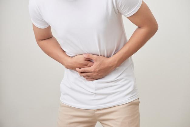 Mensen, gezondheidszorg en gezondheidsprobleem concept - ongelukkige man die lijdt aan buikpijn op witte achtergrond