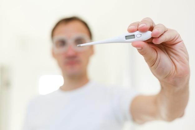 Mensen, gezondheidszorg en koortsconcept, man, thermometer over grijze achtergrond