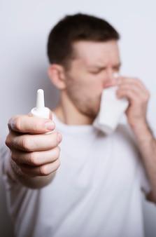 Mensen, gezondheidszorg, rhinitis, koude en allergie concept - zieke man met papier en druppels voor de neus