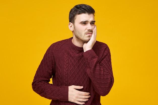 Mensen, gezondheidszorg, tandheelkunde en ziekteconcept. depressieve, verstoorde jonge ongeschoren man met pijnlijke gestreste gezichtsuitdrukking die lijdt aan kiespijn, zich ziek voelt, hand op wang en buik houdt
