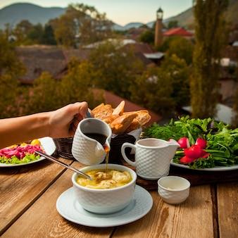 Mensen gietende saus op een heerlijke soepmaaltijd met brood, greens, salade in een kom met dorp op achtergrond, hoge hoekmening.
