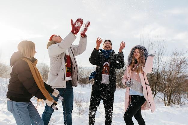 Mensen gooien sneeuw in de lucht