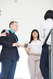 Mensen groeperen drinkin op kantoor