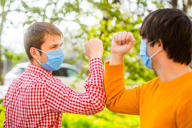 Mensen groeten met ellebogen. mensen dragen buiten een gezichtsmasker.