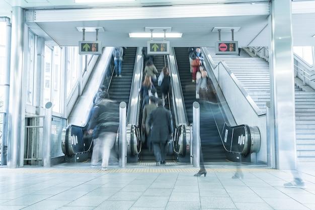 Mensen haasten zich op een roltrap beweging wazig