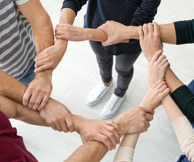 Mensen hand in hand samen, close-up. eenheidsconcept