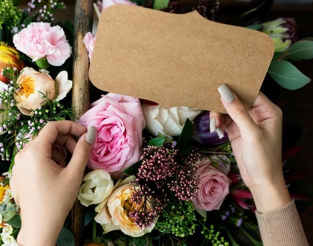 Mensen hand met lege ontwerpruimtekaart met bloemen boeket achtergrond