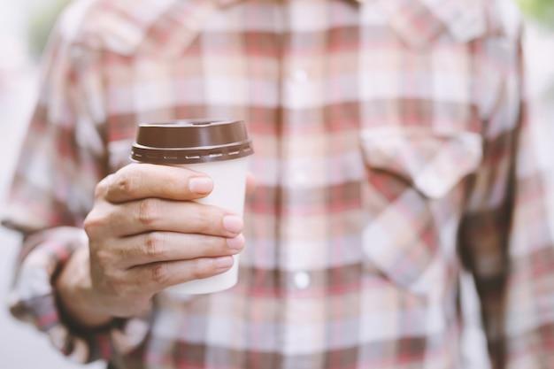Mensen hand met papieren kopje afhaalmaaltijden koffie drinken show op helder hemelsblauw natuurlijk ochtendzonlicht.