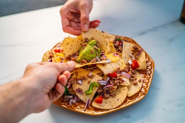 Mensen handen dompelen gele maïs nacho chips gegarneerd met gehakt, guacamole, gesmolten kaas, paprika en korianderblaadjes in plaat op witte stenen tafel