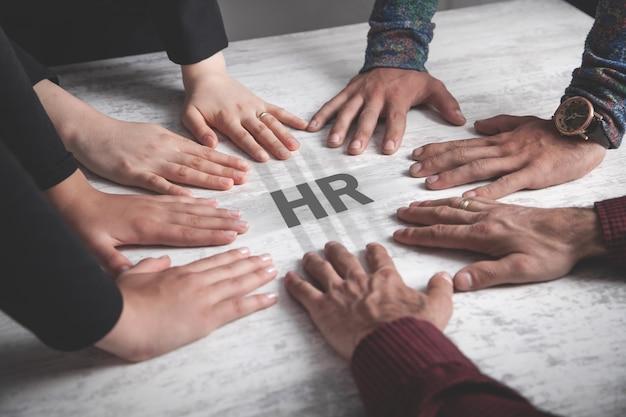 Mensen handen met een hr-woord. personeelszaken. teamwerk Premium Foto