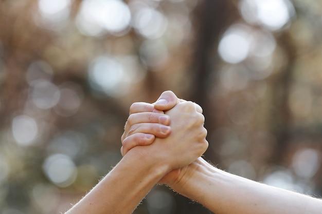 Mensen handen schudden geïsoleerd op een natuurlijke achtergrond in het park. isoleer twee handen die elkaar vasthouden, een signaal van samenwerking.