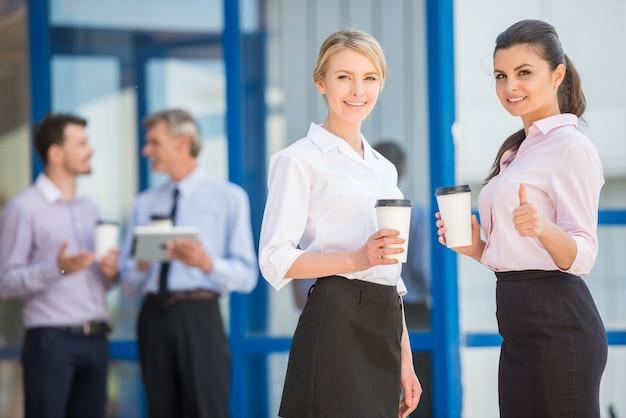 Mensen hebben koffiepauze terwijl ze voor kantoor staan.