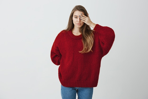 Mensen hebben vaak twee gezichten. binnenschot van aantrekkelijke europese vrouw in rode losse sweater die de helft van gezicht behandelt terwijl zich kalm bevindt, tonend dat zij donkere kant heeft