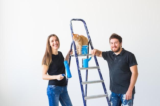 Mensen herinrichting en relatie concept jong grappig koppel met kat doet renovatie in nieuw