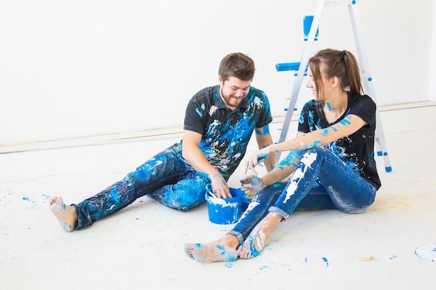 Mensen, herinrichting en relatieconcept - jong grappig stel doet renovatie in nieuw appartement en veel plezier tijdens de pauze.