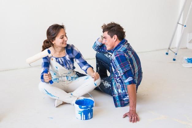 Mensen, herinrichting en relatieconcept - jong grappig stel doet renovatie in nieuw appartement.