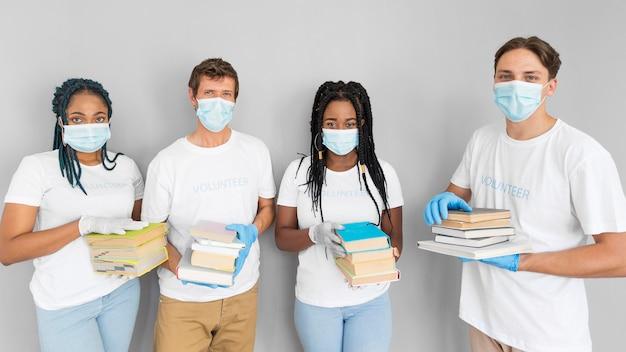 Mensen houden een hoop boeken vast om ze te doneren