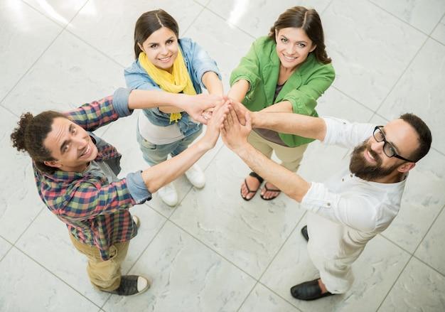 Mensen houden handen bij elkaar en kijken omhoog.