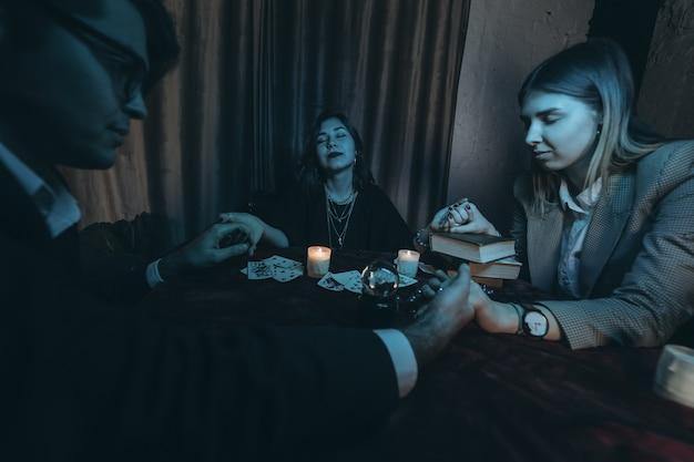 Mensen houden handen van de nacht aan tafel met kaarsen