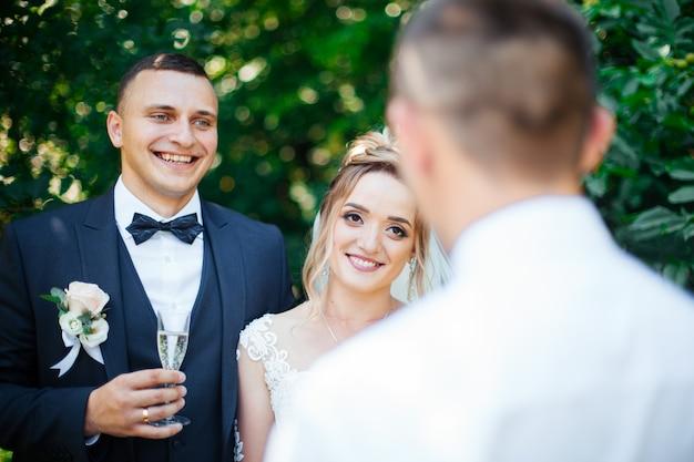 Mensen houden in handen glazen met witte wijn. huwelijksfeest. vrienden roosteren met een champagne