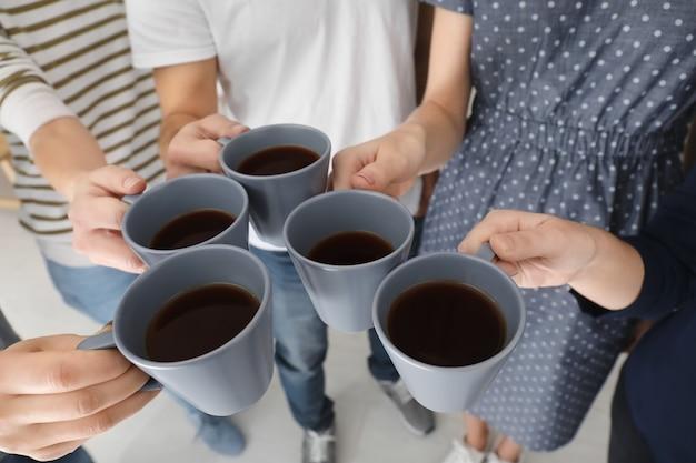 Mensen houden kopjes koffie bij elkaar. eenheid concept