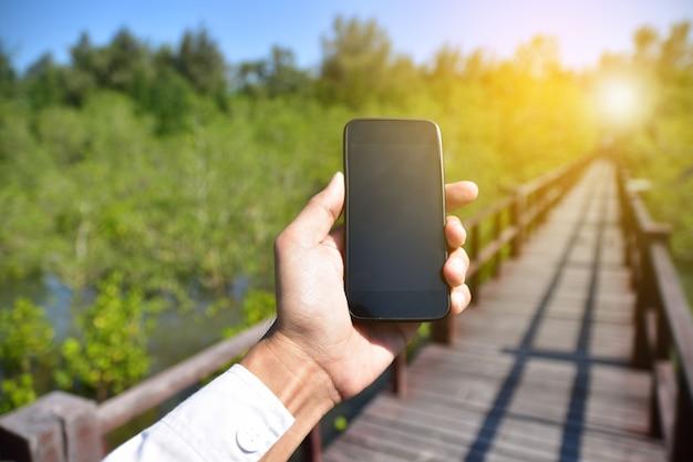 Mensen houden mobiele slimme telefoon op boom achtergrond