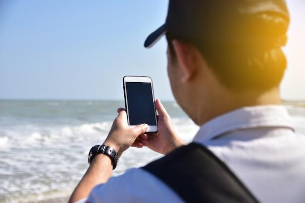 Mensen houden mobiele smart phone op zee achtergrond